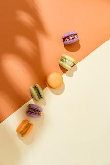 Вид сверху красочного macaron или macaroon на оранжевом бежевом фоне. выборочный фокус. плоская планировка