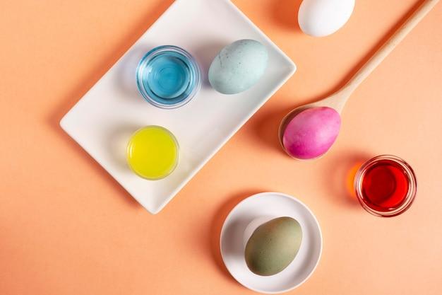 Вид сверху красочных расписных пасхальных яиц с краской