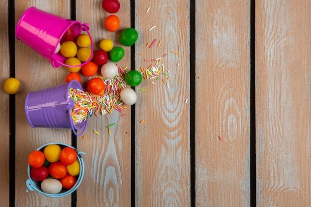 Вид сверху разноцветных брызг и конфет, разбросанных из маленьких ведер
