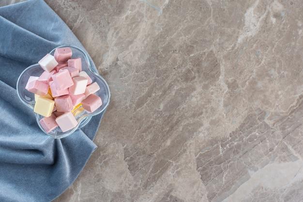 Вид сверху красочных сладких конфет в стеклянной миске над салфеткой.