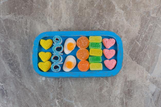 Вид сверху красочных сладких конфет на синей деревянной тарелке.
