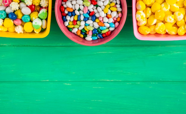 コピースペースを持つ緑の木製の背景にボウルにカラフルな甘い砂糖菓子のトップビュー
