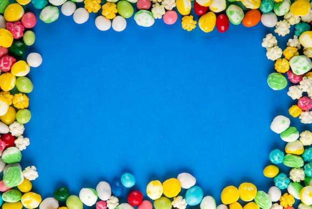 コピースペースを持つ青い木製の背景にカラフルな甘い砂糖菓子のトップビュー