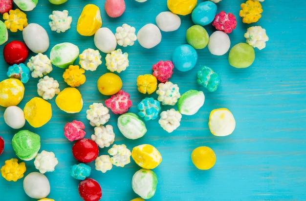 青い木製の背景に散在しているカラフルな甘い砂糖菓子のトップビュー