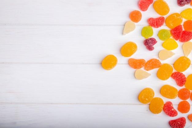 Взгляд сверху красочных вкусных конфет мармелада разбросанных на деревенское
