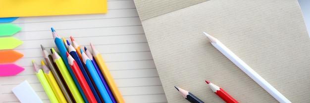 描画用の鉛筆のカラフルなセットの平面図です。テーブルの空のシート。明るいカバーとブックマークが付いたピン。黄色い紙。オフィス文具や消耗品のコンセプト
