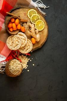 Вид сверху композиции с кукурузным диетическим хлебом кумкватами, палочки корицы, ломтики лимона и имбирь на деревянной доске на черном фоне
