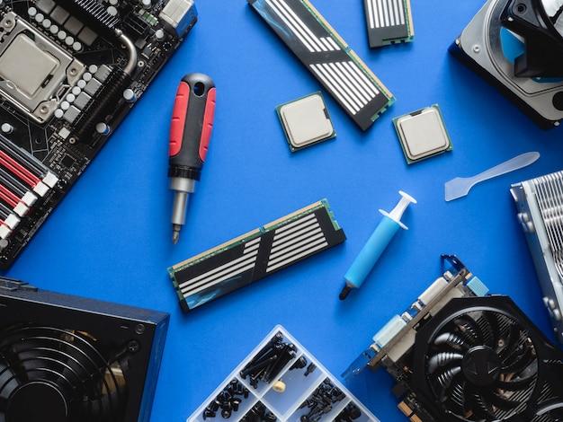 Вид сверху компьютерных частей с жестким диском, оперативной памятью, процессором, видеокартой и материнской платой на синем фоне таблицы.