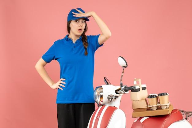 パステル ピーチ色の背景にコーヒーと小さなケーキを乗せたバイクの隣に立っている集中宅配便の女性のトップ ビュー