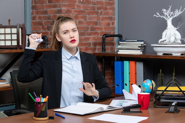 テーブルに座って、オフィスで包まれた紙を保持している集中女性の上面図