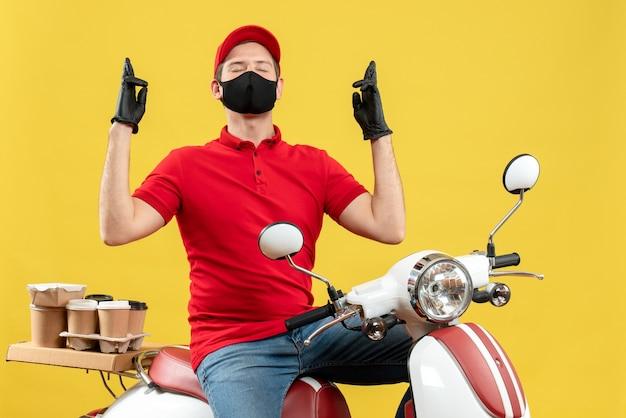医療用マスクで赤いブラウスと帽子の手袋を身に着けている集中した若い大人の平面図は、夢を見てスクーターに座って注文を配信します