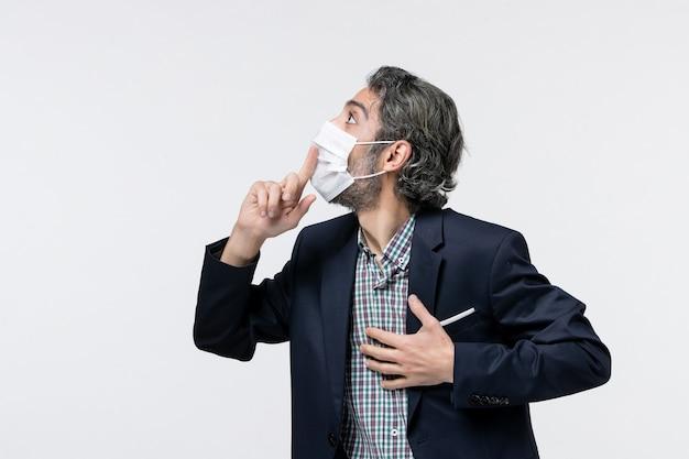 マスクを着用し、白い背景の右側を見上げてスーツを着て集中している若い男の上面図