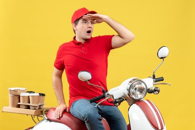 黄色の背景に注文を配信赤いブラウスと帽子を身に着けている集中若い男の上面図