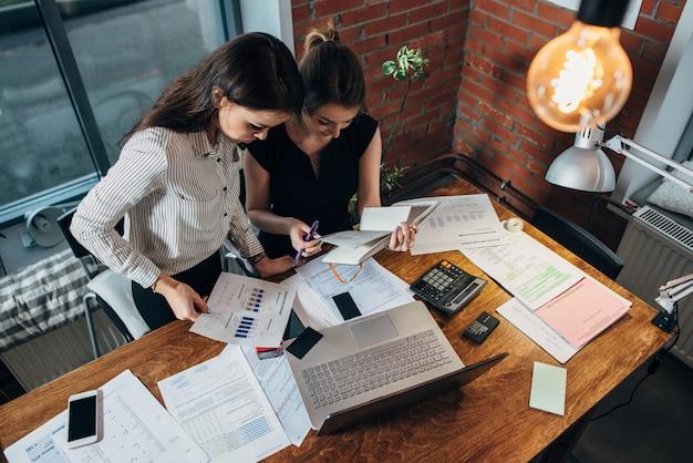 집중된 젊은 여성들이 탁자에 앉아서 함께 일하는 모습을 가장 잘 볼 수 있습니다.