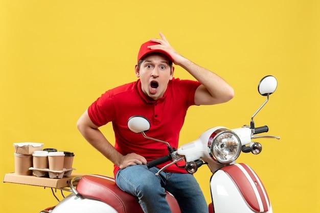 黄色の背景に注文を配信する赤いブラウスと帽子を身に着けている心配している若い男の上面図