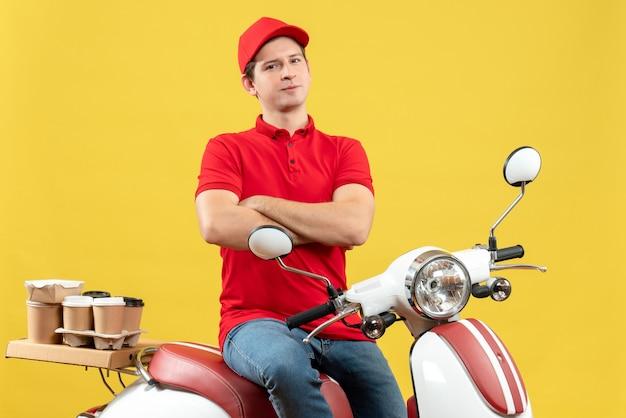 黄色の背景に注文を配信する赤いブラウスと帽子を身に着けている自信を持って野心的な若い男の上面図