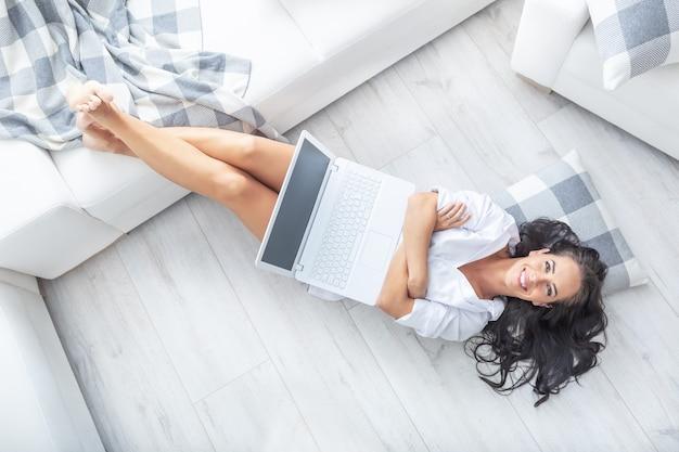 Вид сверху уверенной в себе красивой фрилансера, работающей из дома, одетой только в белую рубашку, с поднятыми ногами и скрещенными на груди руками, улыбаясь, с компьютером на коленях.