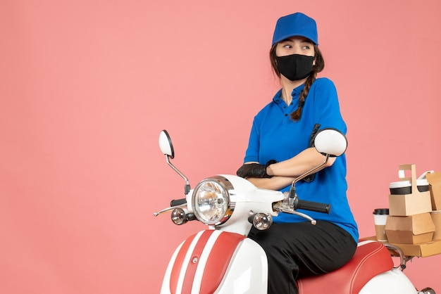파스텔 복숭아 배경에 주문을 제공하는 스쿠터에 앉아 의료 마스크와 장갑을 착용하는 자신감 택배 소녀의 상위 뷰