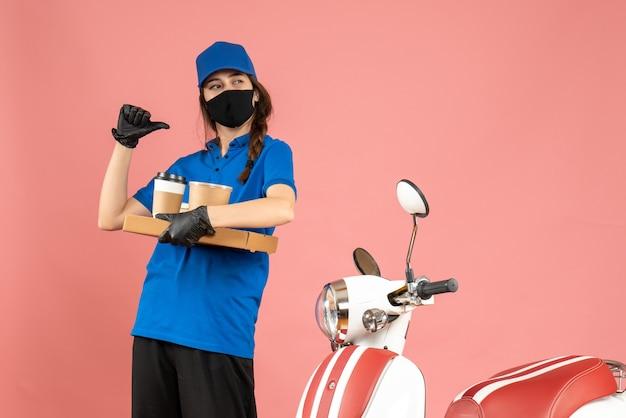 パステル カラーの桃色の背景を指し示すコーヒーの小さなケーキを保持しているオートバイの隣に立っている医療用マスクの手袋を身に着けている自信を持って宅配便の女の子のトップ ビュー