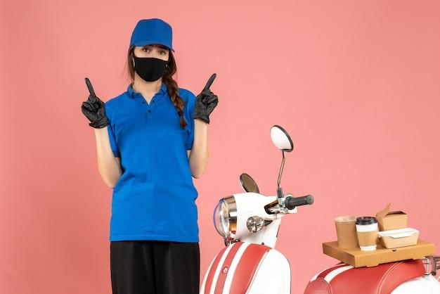 파스텔 복숭아 색 배경에 양쪽을 가리키는 커피 케이크와 함께 오토바이 옆에 서있는 의료 마스크 장갑을 끼고 자신감 택배 소녀의 상위 뷰