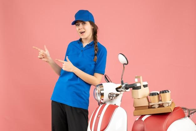 パステル ピーチ色の背景にコーヒーと小さなケーキを乗せたバイクの隣に立っている自信のある宅配便の女性のトップ ビュー