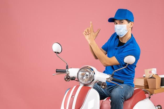 パステル調の桃の背景に銃のジェスチャーをするスクーターに座っている帽子をかぶった医療マスクを着た自信のある宅配便のトップビュー
