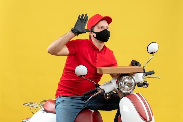 순서를 보여주는 스쿠터에 앉아 의료 마스크에 빨간 블라우스와 모자 장갑을 끼고 자신감 택배 남자의 상위 뷰