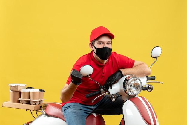 医療用マスクに赤いブラウスと帽子の手袋を着用して、スクーターに座って注文を配信する自信を持って感情的な宅配便の男の上面図