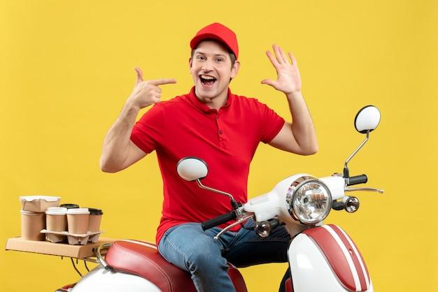 黄色の背景に注文を配信赤いブラウスと帽子を身に着けている自信を持って満足している若い大人の上面図