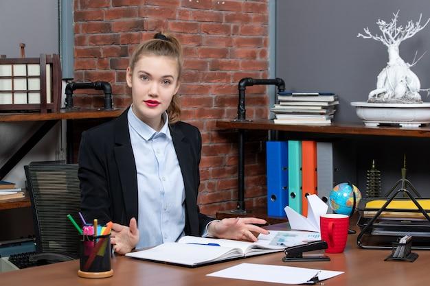 테이블에 앉아 사무실에서 카메라를 위해 포즈를 취하는 자신감 있는 젊은 여성의 상위 뷰