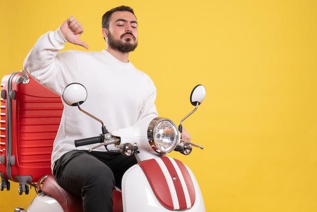 スーツケースを持ってオートバイに座って、孤立した黄色の背景に自分自身を指している自信のある若い男のトップ ビュー