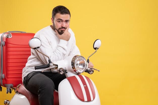 孤立した黄色の背景にスーツケースを持ってオートバイに座っている自信を持って若い男のトップ ビュー