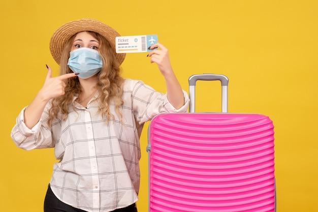 Вид сверху уверенной в себе молодой леди в маске, показывающей билет и стоящей рядом со своей розовой сумкой