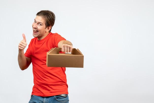 注文を保持し、白い背景で大丈夫ジェスチャーをしている赤いブラウスで自信を持って若い男の上面図