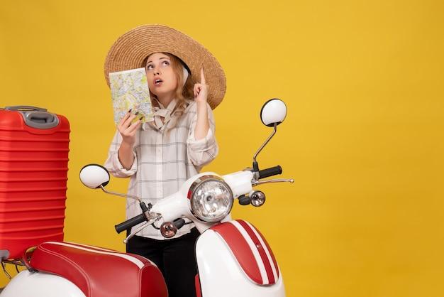 バイクに座って地図を上向きに保持している彼女の荷物を収集する帽子をかぶって自信を持って若い女性の上面図