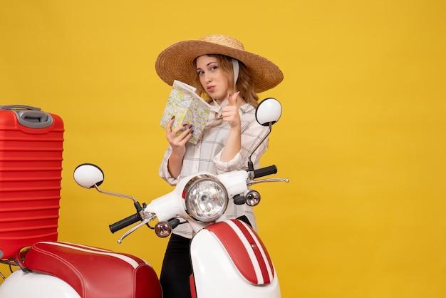 バイクに座って地図を保持している彼女の荷物を収集する帽子をかぶって自信を持って若い女性の上面図