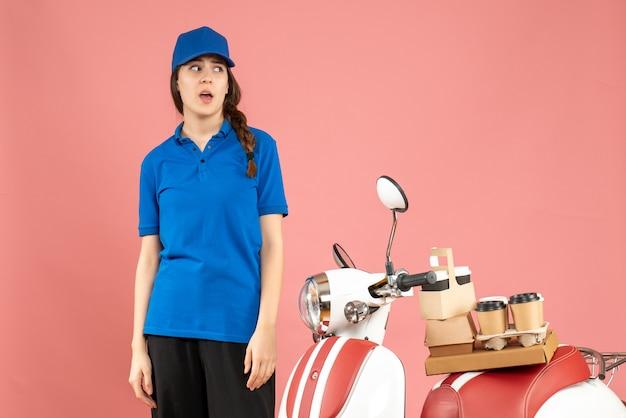 パステル ピーチ色の背景にコーヒーと小さなケーキを乗せたオートバイの隣に立っている混乱した宅配便の女性のトップ ビュー