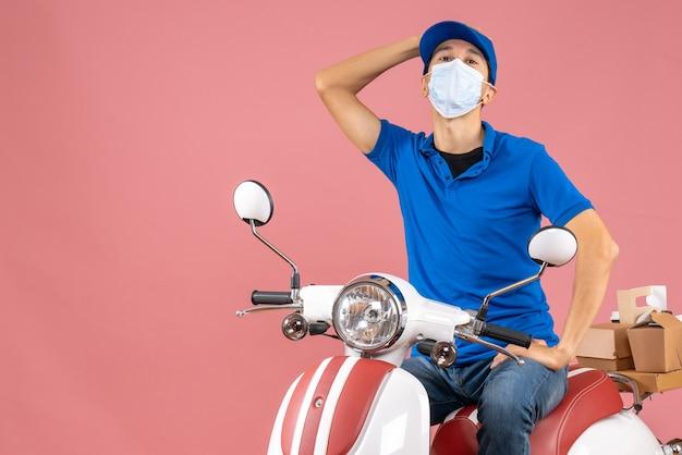 パステル調の桃の背景にスクーターに座っている帽子をかぶった医療マスクを着た混乱した宅配便のトップビュー