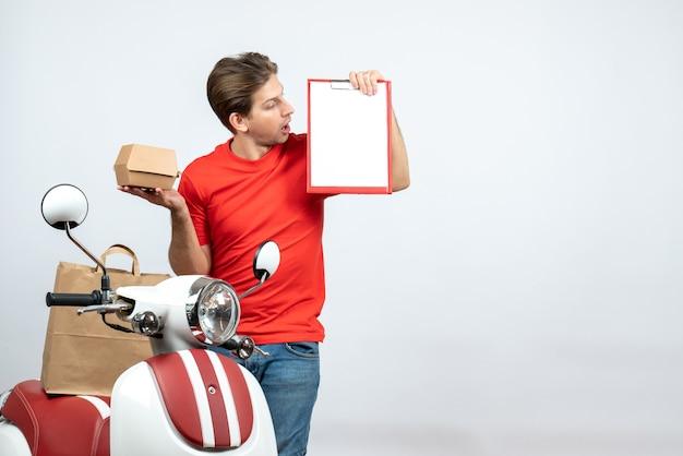 白い背景の上の注文とドキュメントを保持しているスクーターの近くに立っている赤い制服を着た混乱した配達人の上面図