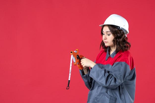 孤立した赤い背景に測定テープを保持しているハード帽子と制服を着た混乱した女性建築家の上面図