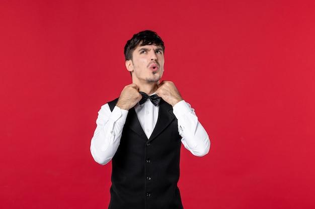 蝶ネクタイと制服を着た混乱した男性ウェイターの上面図