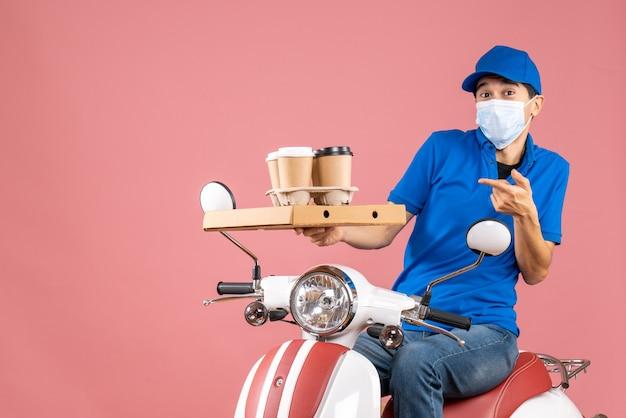 복숭아 배경에 주문을 전달하는 스쿠터에 앉아 모자를 쓰고 마스크에 혼란 스 러 워 놀된 남성 배달 사람의 상위 뷰