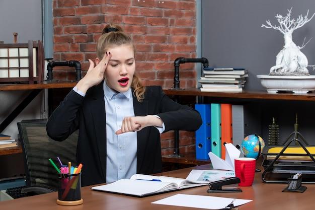 Вид сверху смущенной молодой женщины, сидящей за столом и проверяющей свое время в офисе