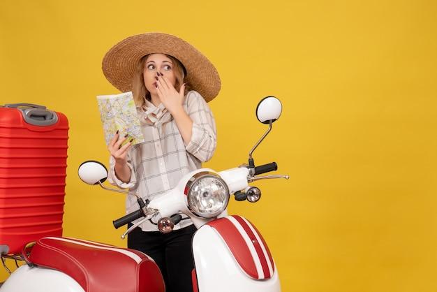 オートバイに座って地図を保持している彼女の荷物を収集する帽子をかぶって混乱している若い女性の上面図