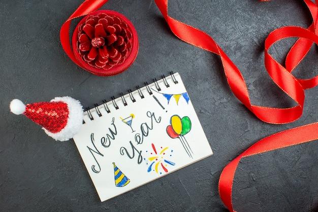 暗い背景に新年の書き込みとサンタクロースの帽子と赤いリボンとノートブックと針葉樹の円錐形の上面図