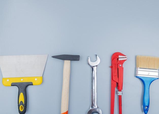 Вид сверху на строительные инструменты, такие как кирпичный молоток, трубный ключ, шпатель, малярная кисть и гаечный ключ, на сером фоне с копией пространства