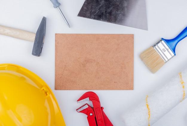 Вид сверху строительных инструментов, таких как кирпичный молоток, защитный шлем, отвертка, трубный ключ, малярная кисть и роликовый шпатель, вокруг плитки метлах на белом фоне