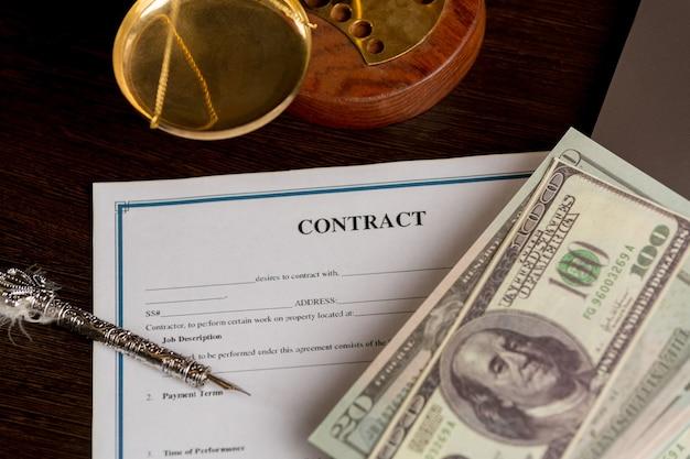 Вид сверху контракта в буфере обмена, лежащем в офисе на деревянном столе с ноутбуком и документами.