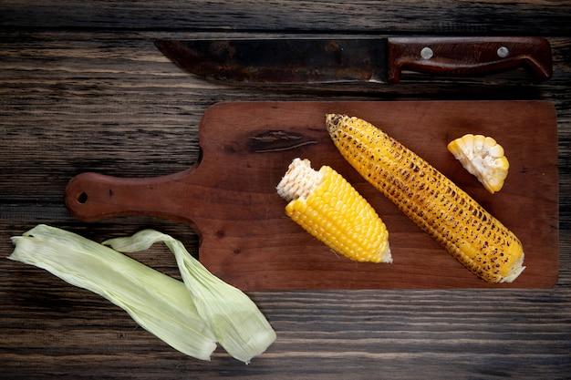木材にトウモロコシの殻とナイフでまな板の上の調理されたトウモロコシのトップビュー