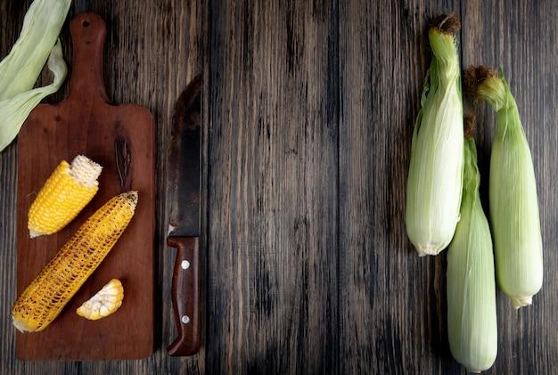 ナイフでまな板の上の調理されたトウモロコシとコピースペースを持つ木材の未調理のトウモロコシのトップビュー